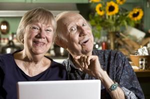 Leende äldre par som utforskar internet